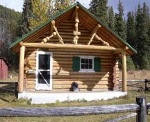 View of the main entrance of Brazeau Warden Cabin, showing the one storey rectangular massing with a overhanging, medium-pitched gable roof over the front to form a porch, 2005.; Parks Canada Agency / Agence Parcs Canada, 2005.