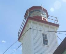 General view of East Ironbound Combined Lighthouse and Dwelling, showing the decorative bracketed cornice supporting the square wood platform and octagonal, cast-iron lantern, 2005.; Public Works and Government Services Canada / Travaux publics et Services gouvernementaux Canada, Don MacDonald, 2005.