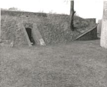View of the east Powder Magazine, showing the low, partially subterranean, inconspicuous massing of the reinforced, rectangular, brick structures, 1989.; Parks Canada Agency / Agence Parcs Canada, 1989.