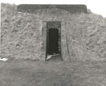 View of the west Powder Magazine, showing the protected entrance flanked by brick sidewalls that slope down to ground level, 1989.; Parks Canada Agency / Agence Parcs Canada, 1989.