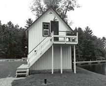 Side view of the Storehouse, Lock Office, showing the exterior wooden staircase, 1989.; Public Works and Government Services Canada / Travaux publics et Services gouvernementaux Canada, 1989.