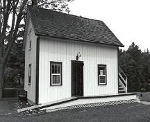 Corner view of the Storehouse, Lock Office, showing the gable roof and board-and-batten wood siding, 1989.; Public Works and Government Services Canada / Travaux publics et Services gouvernementaux Canada, 1989.