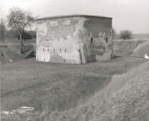 View of the Tower, showing its siting on a flat, grassed area within the fort's earthworks, 1989.; Agence Parcs Canada / Parks Canada Agency, 1989.