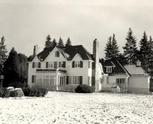 View of the Prime Minister's Cottage, showing its stone fireplaces and open verandah, 1985.; Agence Parcs Canada / Parks Canada Agency, 1985.