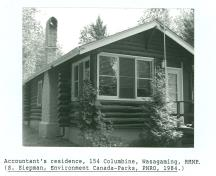 View of the Accountant's Residence, showing its horizontal log construction, 1984.; Agence Parcs Canada / Parks Canada Agency, 1984.