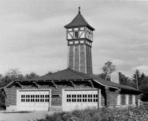 View of the Firehall, showing the intricate log construction, the timber 'crib' containing the garage, the curved hipped roof, and clearly illustrates the prominence of the tower.; Parks Canada Agency / Agence Parcs Canada, n.d.
