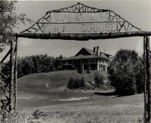 View of the Golf Clubhouse (B7), showing its site on the ridge of a promontory adjacent to the golf course.; Agence Parcs Canada / Parks Canada Agency
