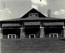 General view of the Golf Clubhouse (B7), showing the horizontal log construction and the cobblestone detailing, 1984.; Agence Parcs Canada / Parks Canada Agency, 1984.