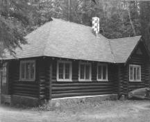 View of the Royal Canadian Air Force Cottage, showing the peeled log walls and shingled roof with chimney, 1984.; Agence Parcs Canada / Parks Canada Agency, 1984.