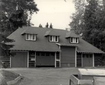 View of Wardens' Equipment Building, showing the broad hipped roof, with exposed rafter-ends and shingle-sided hip roofed dormers, 1984.; Agence Parcs Canada / Parks Canada Agency, 1984.