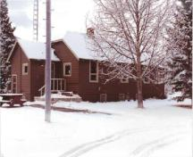 View of the Warden's Residence, showing the wood siding is finished in red-brown paint with light trim, 1992.; Parc national du Canada Banff / Banff National Park of Canada, 1992.