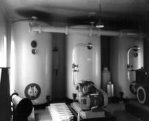 Interior view of the Fog Alarm building, showing the surviving machinery, 1990.; Parks Canada Agency / Agence Parcs Canada, 1990.
