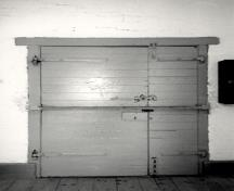 View of the interior of the Barrack, showing the metal door and door hardware, 1990.; Parks Canada Agency / Agence Parcs Canada, 1990.