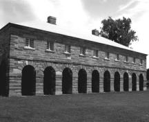 View of the front façade of the Guardhouse, showing the architectural composition of the building, which consists of a rectangular plan, arcaded portico and hipped roof.; Parks Canada Agency / Agence Parcs Canada.