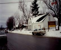 View of the exterior of the St. Laurent Store and Warehouse, showing the wood clapboard siding painted white and the gable roofs without dormers, 1993.; Parks Canada Agency / Agence Parcs Canada, 1993.