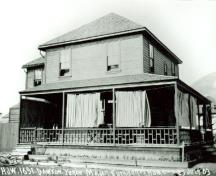 Side view of the Commanding Officer's Residence, showing the low hipped-roof with shingles, strong roof lines, and a full width verandah, 1903.; Library and Archives Canada/ Bibliothèque et Archives Canada, 1903.