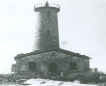 General view of the Lighthouse at Mohawk Island, showing the hammer-dressed finish on the stone walls of the tower and dwelling, giving a heavily rusticated appearance, before 1965.; Department of the Environment / Ministère de l'Environnement, before 1965 / avant 1965.