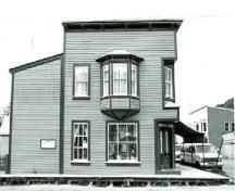 Side view of Mme. Tremblay's Store, showing the inset and splayed corner window, and the oriel window, 1987.; Department of the Environment / Ministère de l'Environnement, 1987.