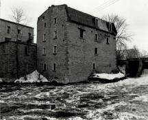 View of the West Mill, showing the exterior walls of stone, 1972.; Agence Parcs Canada / Parks Canada Agency, 1972.
