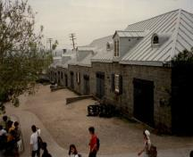 View of the Cannon Carriage Store, showing the hipped roof of sheet metal with batten seams, and the semicircular dormers above the doors, 1991.; Agence Parcs Canada / Parks Canada Agency, 1991.