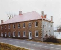 General view of the Carillon Barracks, showing the multi-paned, wooden sash windows along the side façade, 1977.; Parks Canada Agency / Agence Parcs Canada, 1977.
