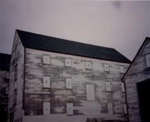 Side elevation of Ryan Fish Storage, showing the clapboard walls that are outlined by finely proportioned trim, 1993.; Agence Parcs Canada / Parks Canada Agency, 1993.