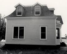 Side view of St. Andrew's Manse, showing the mansard-roofed main structure and the projecting dormers, 1987.; Parks Canada Agency / Agence Parcs Canada, 1987.