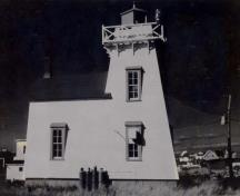 General view of the Tower, showing the rectangular footprint and massing which is comprised of a square, tapered medium-height tower smoothly joined to the tapered sides of a dwelling with a shingled gable roof.; Parks Canada Agency / Agence Parcs Canada.
