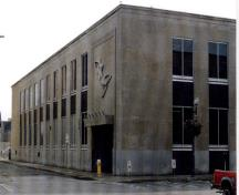 East entrance of the Government of Canada Building, showing the recessed entrance screen under a projecting stone canopy, with figurative sculpture mounted on the limestone wall, framed by a raised moulding, 1998.; Public Works and Government Services Canada / Travaux publics et Services gouvernementaux Canada, 1998.