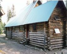 Rear elevation of the Stanley Mitchell Alpine Hut, showing the horizontally laid, peeled round logs with saddle-notched corners, 1998.; Parks Canada Agency/Agence Parcs Canada, 1998.