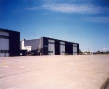 View of the Royal Canadian Air Force Hangar 8, showing the large open expanses of paved aprons and taxiways, 1998.; Department of National Defence / Ministère de la Défense nationale, 1998.