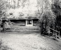 Side view of the Robert Service Cabin, showing the rustic, low-lying form, 1987.; Parks Canada Agency / Agence Parcs Canada, 1987.