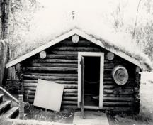Side view of the Robert Service Cabin, showing the log construction with logs chinked with moss to keep out the sub-arctic cold, 1987.; Parks Canada Agency / Agence Parcs Canada, 1987.