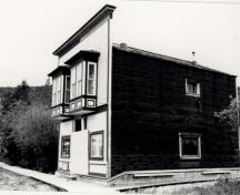 General view of Ruby's Place, showing the horizontal, painted, coved siding of the street façade with its distinctive, large oriel windows, 1987.; Parks Canada Agency / Agence Parcs Canada, 1987.