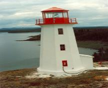 Side elevation of the Tower at the Lightstation, showing its octagonal lantern with a low pitched roof, Battle Island 1990.; Canadian Coast Guard / Garde côtière canadienne, 1990.