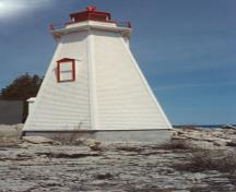 View of the exterior of the Light Tower, showing the white painted, narrow, wood shingle siding, 1990.; Department of Transport / Ministère des Transports, 1990.