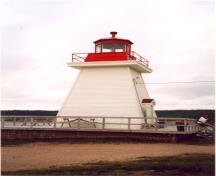 Side view of the Coastal Lighthouse, showing the metal railing at the gallery level and the octagonal metal lantern, 2000.; Department of Fisheries and Oceans / Ministère des Pêches et des Océans, 2000.