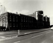 View of the Bay Street Armoury, showing the crenellated parapet walls that crown the building, 1990.; Ministère de la Défense nationale / Department of National Defence, 1990