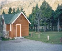Corner view of Comfort Station 6, showing the cross-gable roof and the use of half-log slab siding for the walls, 1990.; Parks Canada Agency / Agence Parcs Canada, 1990.