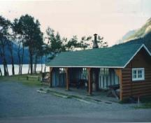 General view of Kitchen Shelter 2, showing the moderately pitched gabled roof with exposed rafters and log slab siding for the walls, 1990.; Parks Canada Agency / Agence Parcs Canada, 1990.