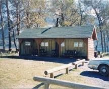 General view of Kitchen Shelter 6, showing the moderately pitched gabled roof with exposed rafters and log slab siding for the walls, 1990.; Parks Canada Agency / Agence Parcs Canada, 1990.
