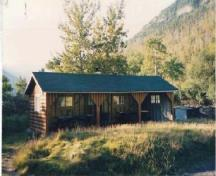 General view of Kitchen Shelter 7, showing the simple, low massing of the one-storey, three-sided structure, 1990.; Parks Canada Agency / Agence Parcs Canada, 1990.