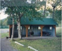 General view of Kitchen Shelter 8, showing the squared timbers used as posts within the open front, 1990.; Parks Canada Agency / Agence Parcs Canada, 1990.