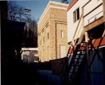 View of the Transformer House, showing its brick massing, flat roof, and well-defined concrete foundation, 1991.; Travaux publics Canada / Public Works Canada, 1991.
