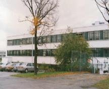 General view of Building M-12, showing the reinforced concrete construction and white stucco clad exterior walls, 1990.; National Research Council Canada / Conseil national de recherches du Canada, 1990.