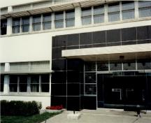 "View of the main entrance to Building M-20, showing the use of smooth ""modern"" materials such as steel, glass block, white stucco and black marble veneer, 1991.; Parks Canada Agency / Agence Parcs Canada, J. Adell, 1991."