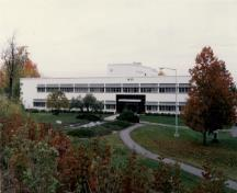 General view of Building M-20, showing the low massing of the main two-storey block with three, three-storey wings and flat roof, 1990.; National Research Council of Canada / Conseil national de recherches du Canada, 1990.