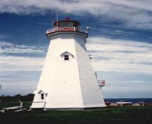 View of the exterior of the Tower, showing the red-painted steel lantern that is appropriately proportioned to the tower and the distinctive cross-braced wood railing, 1990.; Transport Canada / Transports Canada, 1990.