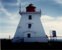 Side view of the Light Tower, showing the classical detailing of the bracketed cornice and the vertical alignment of the tall, slightly projecting shed and gable roofed windows and door, circa 1990.; Transport Canada / Transports Canada, circa / vers 1990.