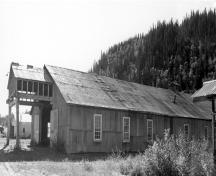 General view of the Machine Shop, showing its simple rectangular shape, its gable roof and its corrugated metal siding and roof covering, 1988.; Parks Canada Agency / Agence Parcs Canada, 1988.